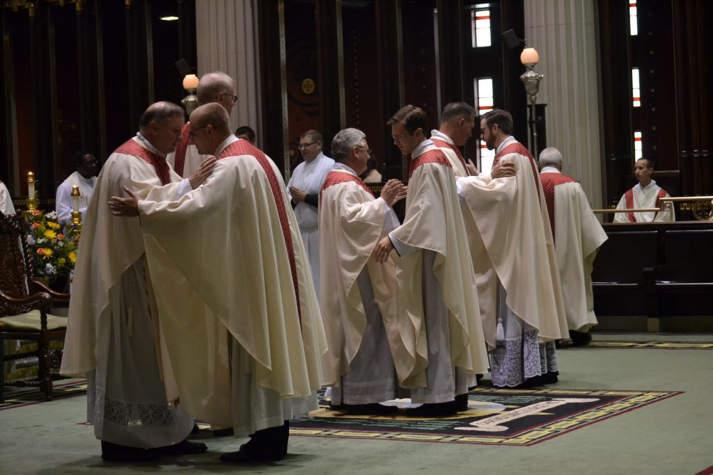 The priests in the sanctuary welcome the newly ordained into the order of presbyters (CT Photo/Greg Hartman)