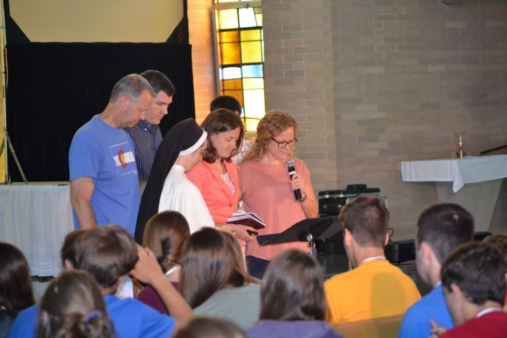 The team prays over the morning keynote speaker Jacquie Lustig. (CT Photo/Greg Hartman)