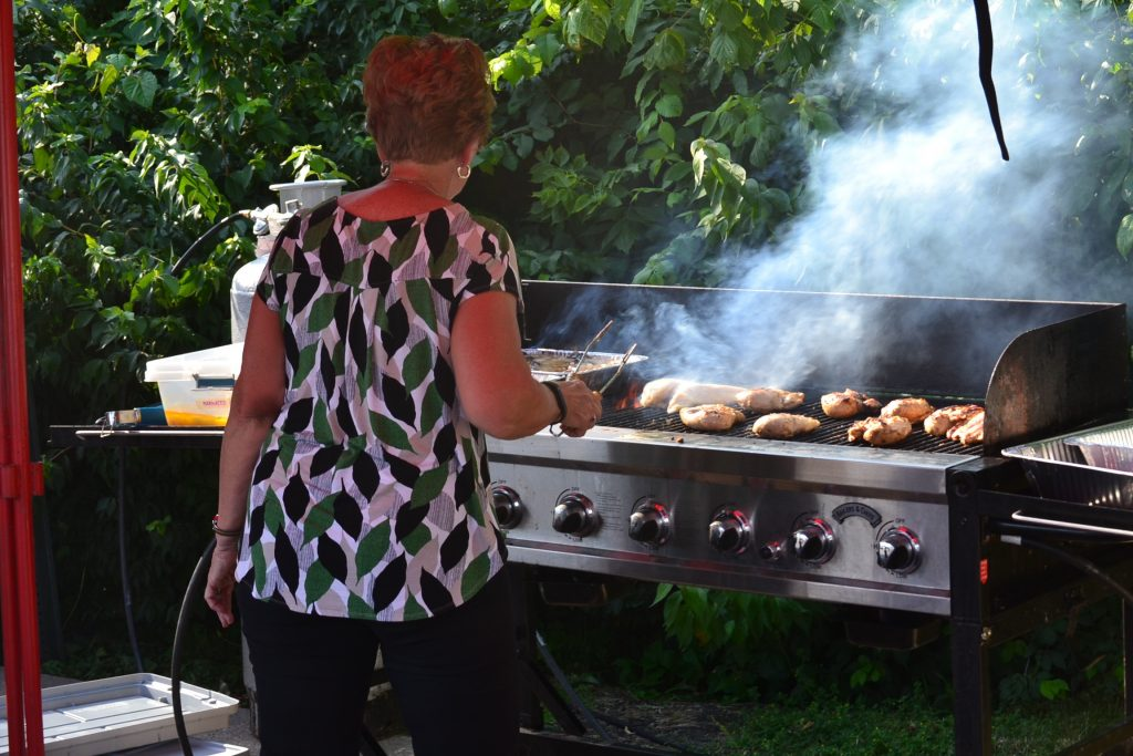 Among many delicious menu items at Gertie's Grill, volunteer readies the chicken. (CT Photo/Greg Hartman)