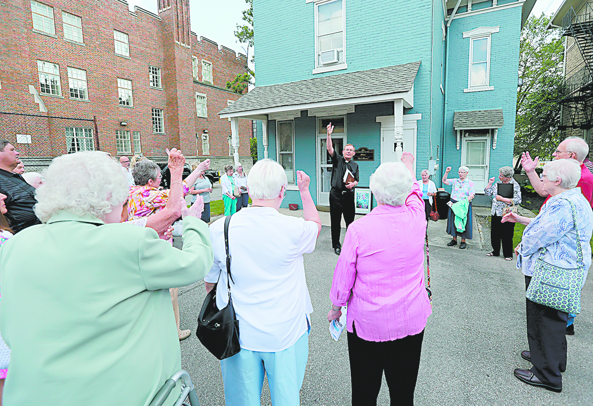 """Rev. Michael Pucke. pastor of St. Julie Billiart Catholic Parish in Hamilton, leads a cheer to Sr. Dorothy during the blessing of """"The Sr. Dorothy Stang House"""", a house for homeless families, during a dedication ceremony in Hamilton Saturday, May 27, 2017. (CT Photo/E.L. Hubbard)"""