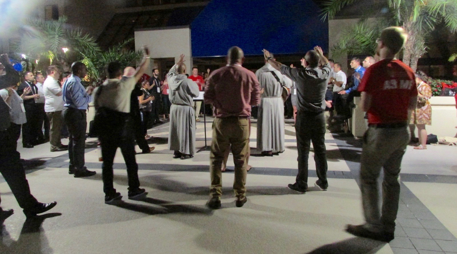 About 75 people joined two priests from the Franciscan Friars of the Renewal for impromptu charismatic prayer in a plaza next to a hotel pool one night (CT Photo/Gail Finke)