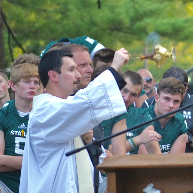 Father Ruiz at Benediction with the McNicholas Football Rockets looking on. (CT Photo/Gail Finke)