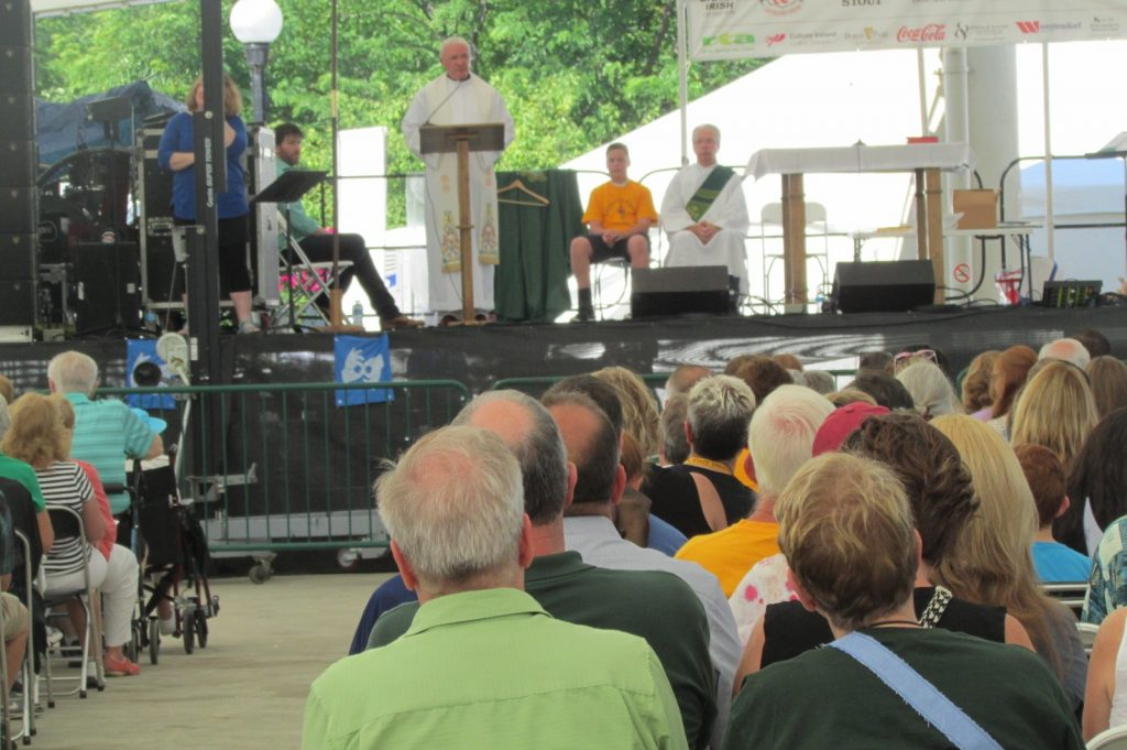 Father David Byrne celebrates Mass. Also on the stage/sanctuary: a sign language interpreter from the festival, two unidentified men who read the first two readings, and Deacon Michael Leo (CT Photo/Gail Finke)