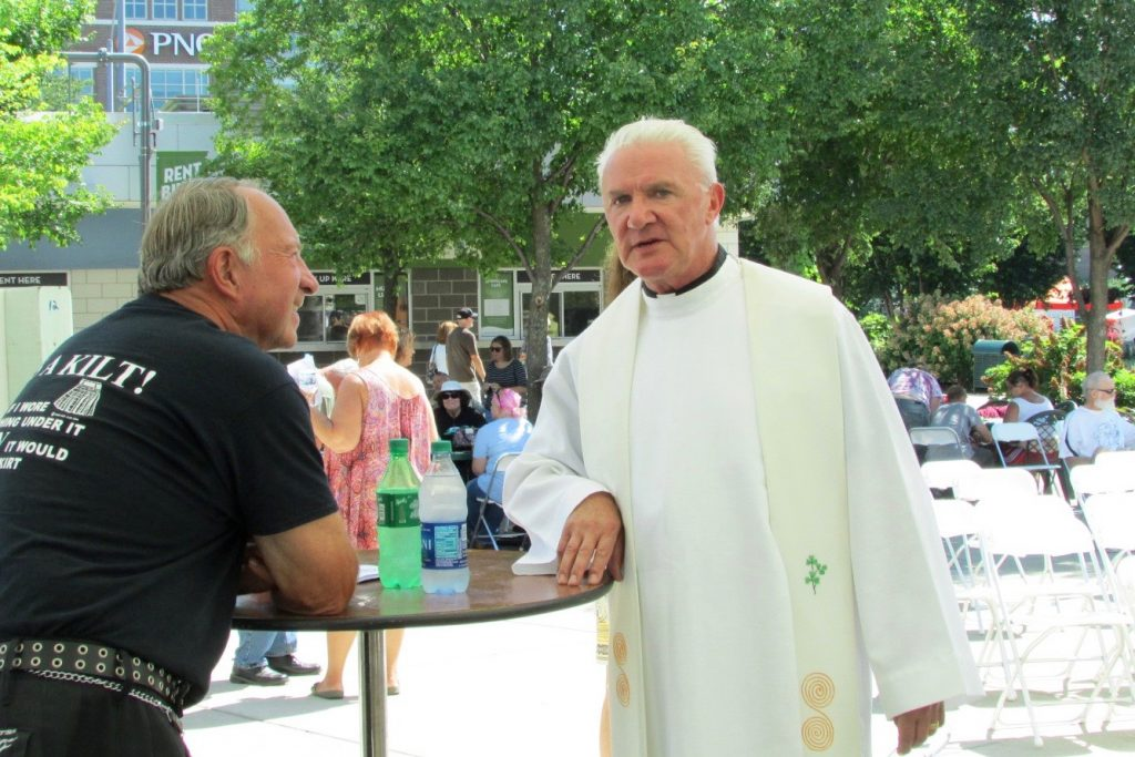 Father Byrne speaks to a kilt-clad gentleman following the outdoor Mass (CT Photo/Gail Finke)