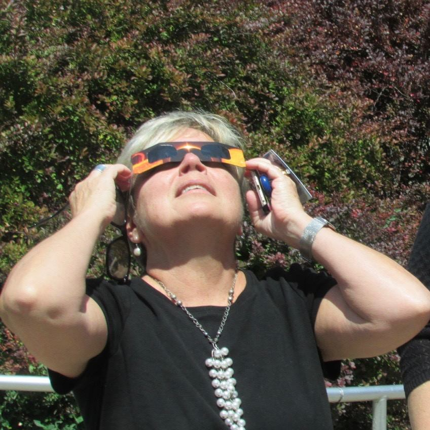 Archdiocese of Cincinnati employee Sarah Frohmiller takes a look at the 2017 partial solar eclipse. (CT Photo/Gail Finke)