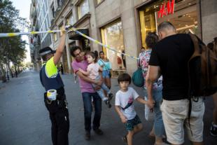 A police officer helps evacuate people after a van crashed into pedestrians in the Las Ramblas district of Barcelona, Spain, Aug. 17. Terrorists killed at least 12 and injured more than 50 others. (CNS photo/Ana Jimenez, La Vanguardia via Reuters)