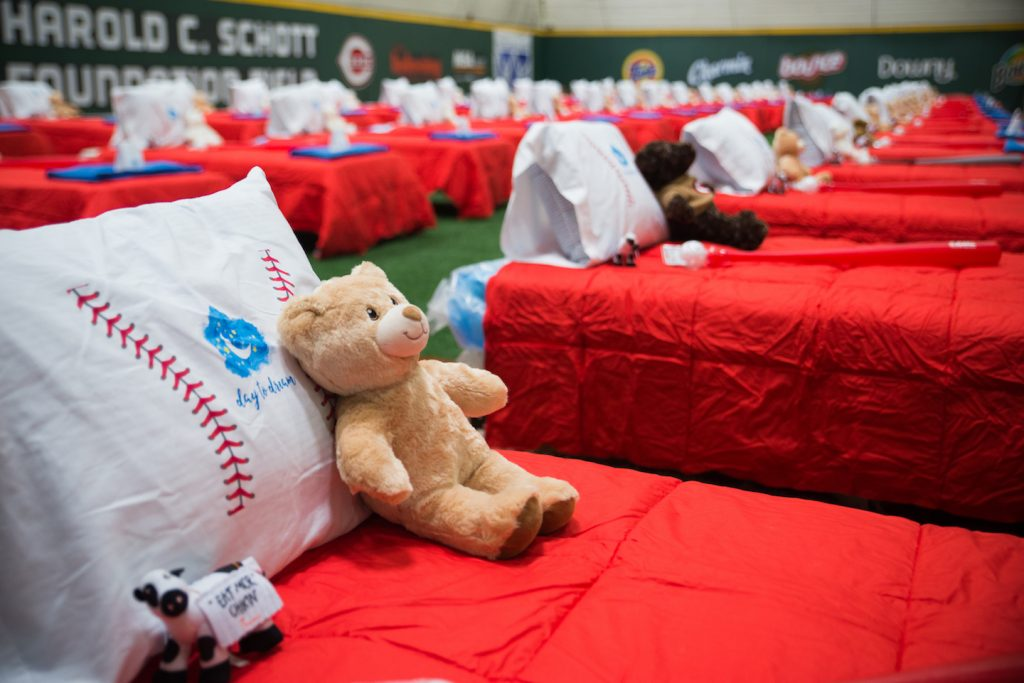Fifty beds await their new owners. Made up with red comforters and baseball-print pillowcases, each also came with a teddy bear, a stuffed cow, and a bat