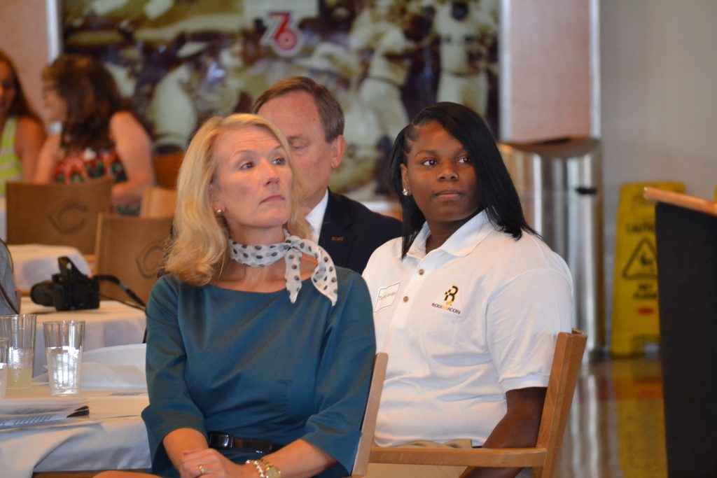 CISE Student Tionna Jordan from Roger Bacon is seated with Jill Meyer after her address to the crowd on her journey in Catholic Schools. (CT Photo/Greg Hartman)