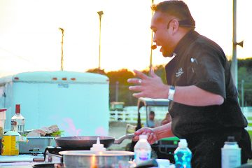 """Deglazing a rich tomato sauce with vodka and burning off the alcohol, Father Leo Patalinghug told the crowd when Jesus sent the apostles to evangelize the world, he told them to eat whatever they were offered wherever they stayed. """"Christians can eat and drink whatever they like,"""" he said, """"in moderation."""" (CT Photo/Steve Trosley)"""