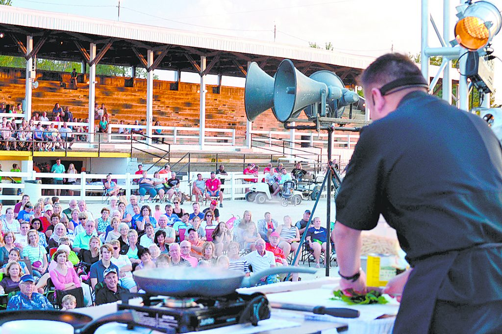 Father Leo Patalinghug, prepares penne pasta with vodka sauce for a crowd at the Mercer County Fair in Celina Aug. 13. It was Father Leo's first county fair appearance. He launched his cooking ministry shortly after the 9-11 tragedy interrupted a planned trip to France and set in motion a series of events that helped him discern his apostolate to strengthen families and communities around the dinner table. (CT Photo/Steve Trosley)