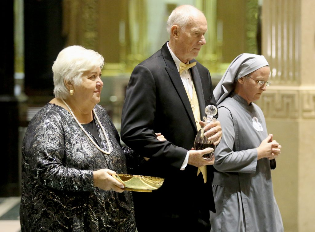 Gert and Gerry Patterson bring up the offertory gifts during the Golden Jubilee Mass at the cathedral accompanied by their daughter, Sister Mary Mediatrix of All Grace, a member of the Society of Our Lady of the Most Holy Trinity. (CT Photo/E L Hubbard)
