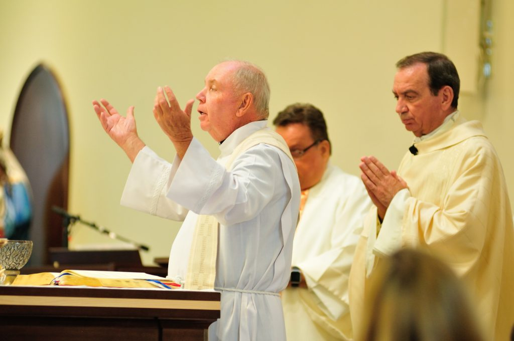 The pastor, Father Jim Manning, prays with Archbishop Dennis J. Schnurr at the Mass celebrating the parish's 150th anniversary and the new church building's first anniversary. (CT Photo/Jeff Unroe)
