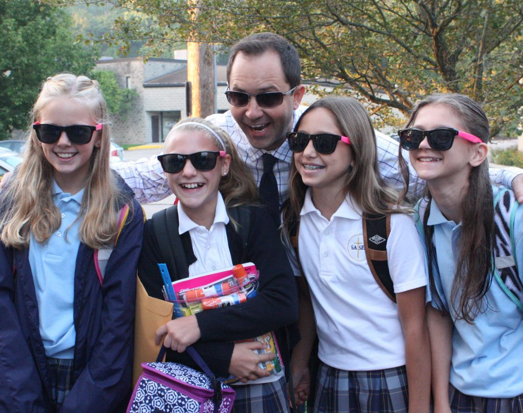 St. Andrew – St. Elizabeth Ann Seton School's principal, Mr. Mark Wilburn, greeted sixth grade students, Sydnie Reith of Goshen, Avery May of Goshen, Grace Evans of Milford and Marin Warman of Goshen each with a pair of cool shades on their first day of the new school year. (Courtesy Photo)