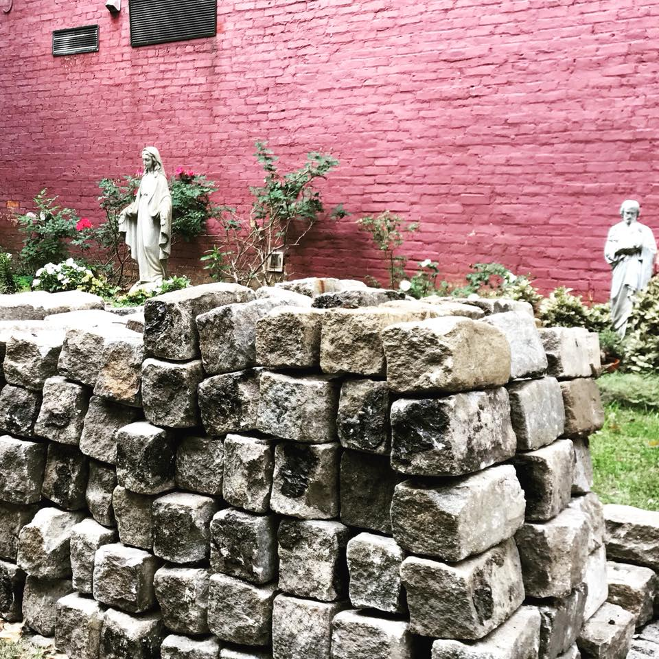 Cleaned up: The bricks (mortar removed) stacked neatly in the courtyard garden, under the watchful eyes of Mary and St. Joseph. COURTESY PHOTO