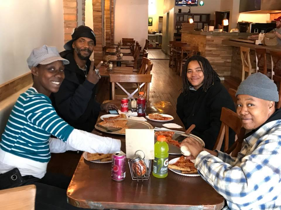 A man walking by stopped to ask what had happened, and bought lunch for the five people remaining in the volunteer cleanup grew. Here they pose at Lucy Blue Pizza down the street. COURTESY PHOTO