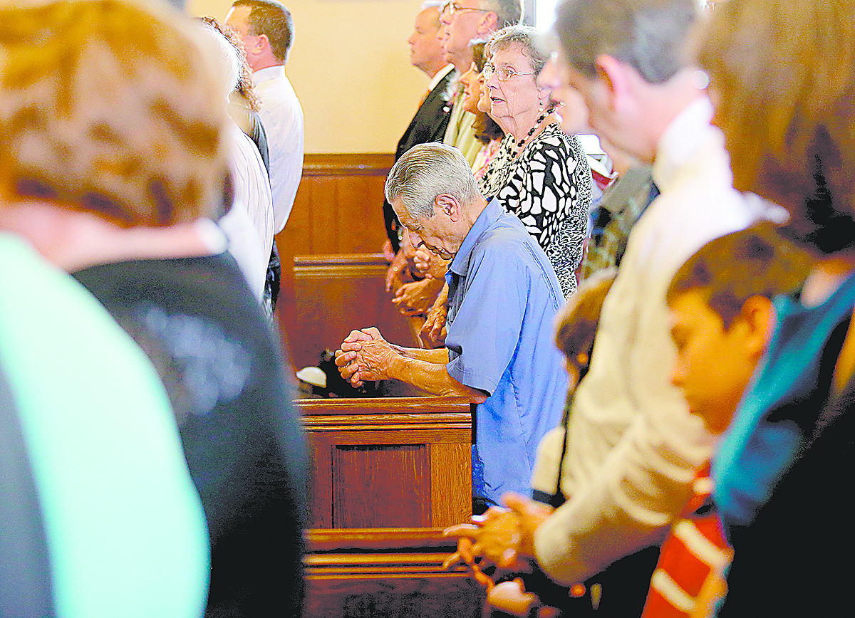 A parishioner kneels in prayer during the Feast of St. Bernard Mass and the closing of the One Hundred and Fiftieth Anniversary Year at St. Bernard of Clairvaux Catholic Church in Cincinnati Saturday, Aug. 19, 2017. (CT Photo/E.L. Hubbard)