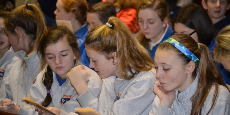 Students looking over the program for the Catholic Schools Week Mass (CT Photo/Greg Hartman)