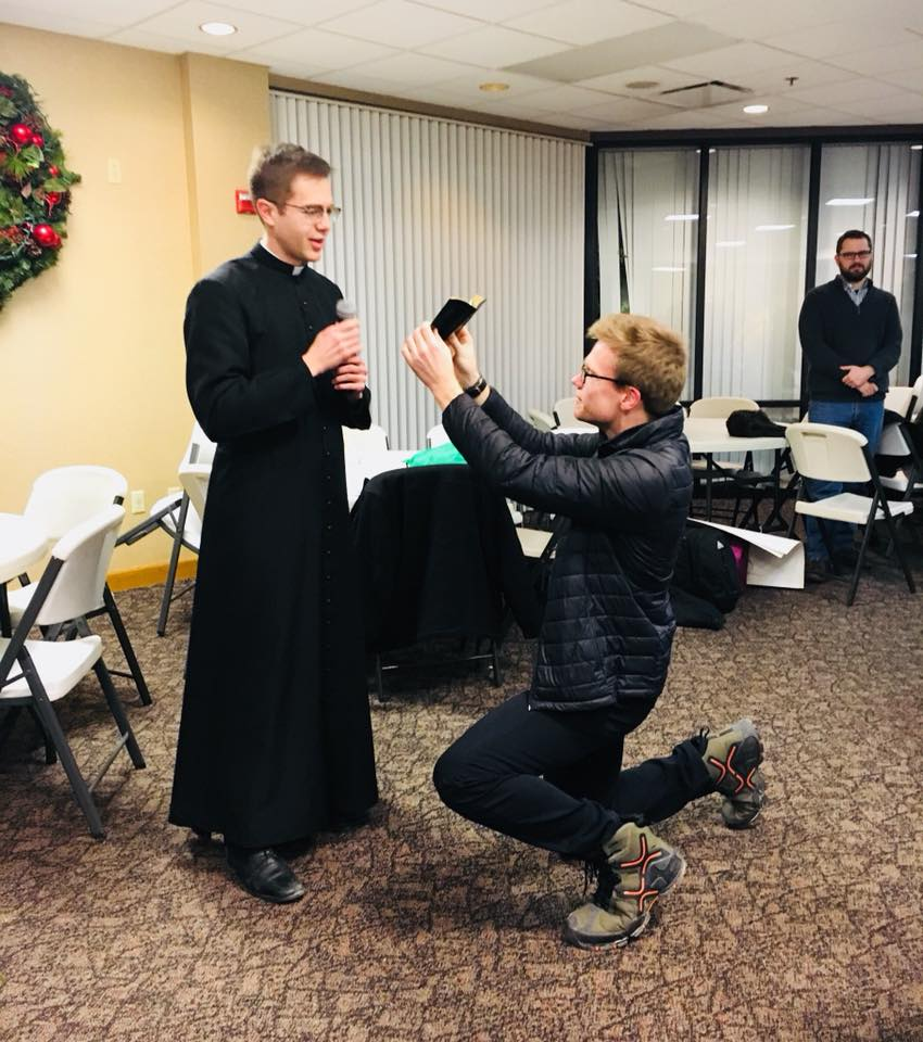 Prayer for March for Life 2018 at Lehman High School, Father Ethan Moore holds prayer book for Father Peter Langenkamp (Courtesy Photo)