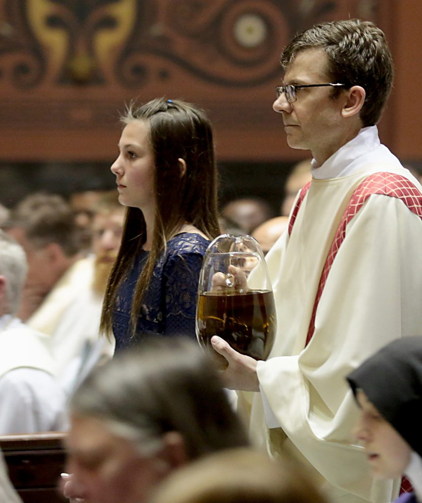 Hope Cromer and Deacon Craig Best present the Sacred Chrism Oil during the Chrism Mass at the Cathedral of Saint Peter in Chains in Cincinnati Tuesday, Mar. 27, 2018. (CT Photo/E.L. Hubbard)