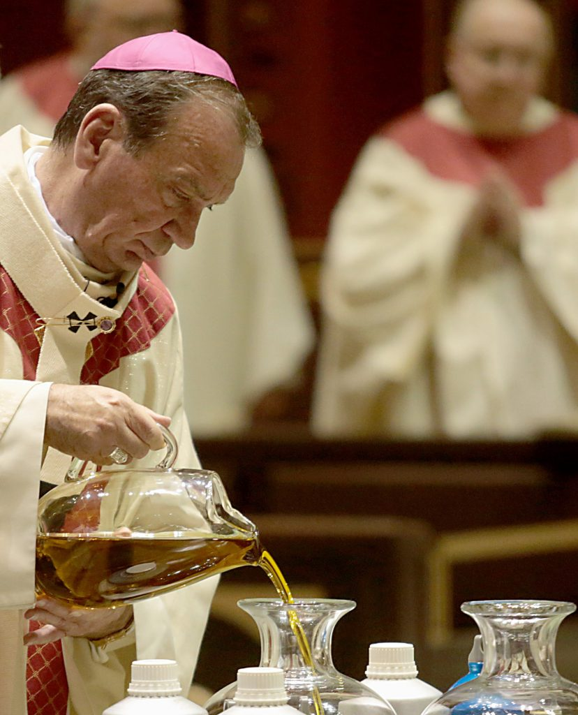 Archbishop Dennis Schnurr pours the Sacred Chrism Oil during the Chrism Mass at the Cathedral of Saint Peter in Chains in Cincinnati Tuesday, Mar. 27, 2018. (CT Photo/E.L. Hubbard)