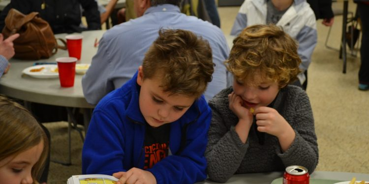 Having fun and reading a picture book at the St. Cecilia Fish Fry 2018 (CT Photo/Greg Hartman)