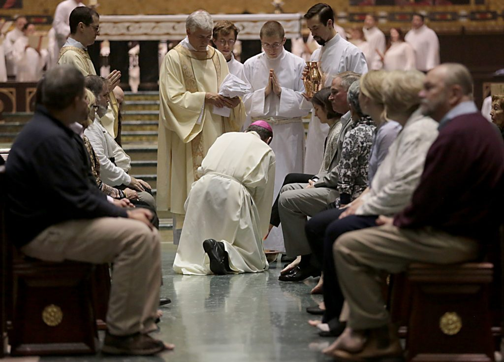Archbishop Dennis Schnurr kneels to wash the feet of a parishioner during the Solemn Evening Mass of the Lord's Supper on Holy Thursday at the Cathedral of Saint Peter in Chains Cathedral in Cincinnati March 29, 2018. (CT Photo/E.L. Hubbard)