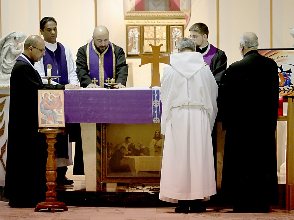 Faith leaders place their hands on the Altar before giving each other, and then those gathered, the Sign of Peace during the Lenten Prayer Service for Christian Unity and Religious Freedom at St. Anthony of Padua Maronite Catholic Church in Cincinnati Saturday, Mar. 10, 2018. (CT Photo/E.L. Hubbard)