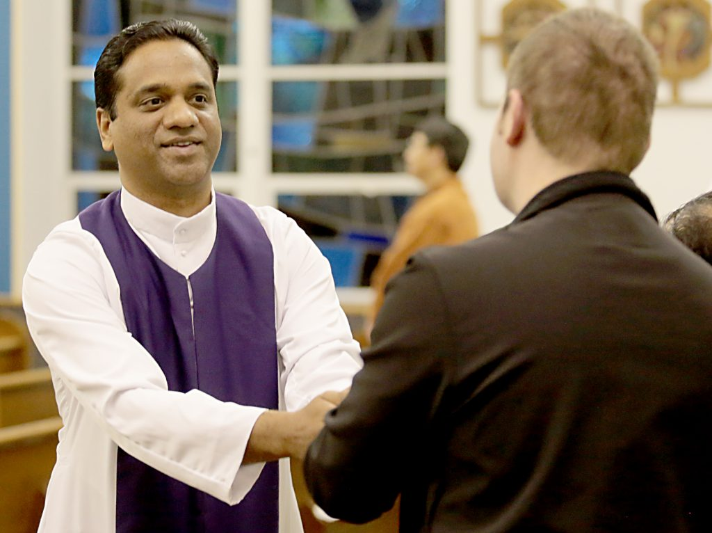 Fr. Jiby Antony Thekkemuriyil, from St. Chavara Syro-Malabar Catholic Mission in Cincinnati, greets a parishioner with the Sign of Peace during the Lenten Prayer Service for Christian Unity and Religious Freedom at St. Anthony of Padua Maronite Catholic Church in Cincinnati Saturday, Mar. 10, 2018. (CT Photo/E.L. Hubbard)