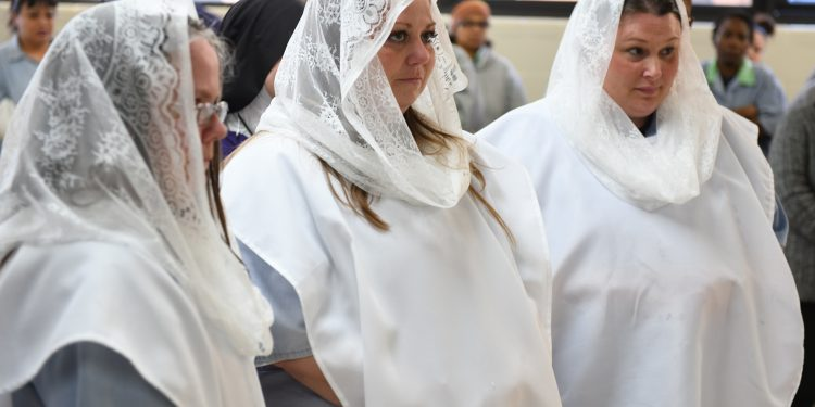 Newly baptized members Teri, Lee Anna and Mincey at Easter Mass (CT Photo/Mark Bowen)