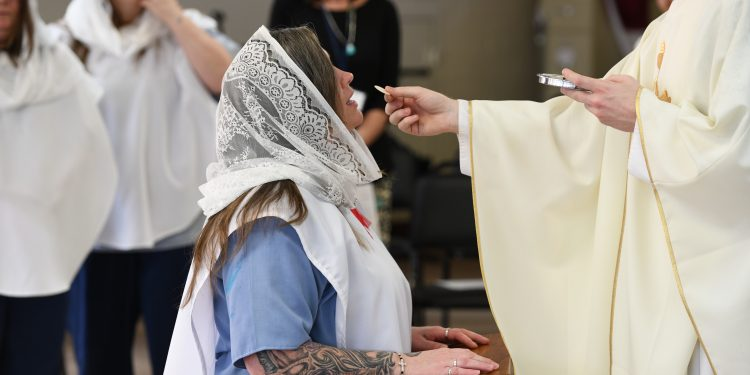 Teri Simon receives First Communion during Easter Mass. (CT Photo/Mark Bowen)