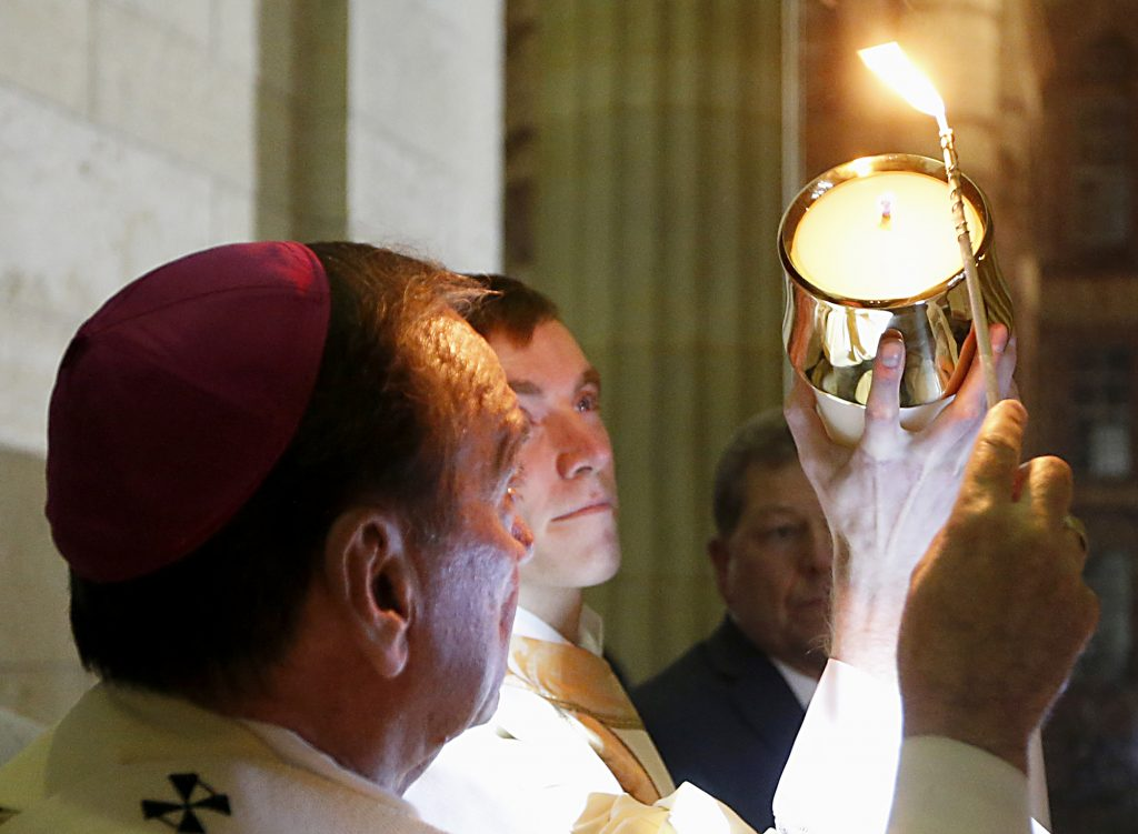 Archbishop Dennis Schnurr lights the Easter Candle, held by Deacon Jacob Willig, for the Easter Vigil in the Holy Night at the Cathedral of Saint Peter in Chains in Cincinnati, Holy Saturday, March 31, 2018. (CT Photo/E.L. Hubbard)