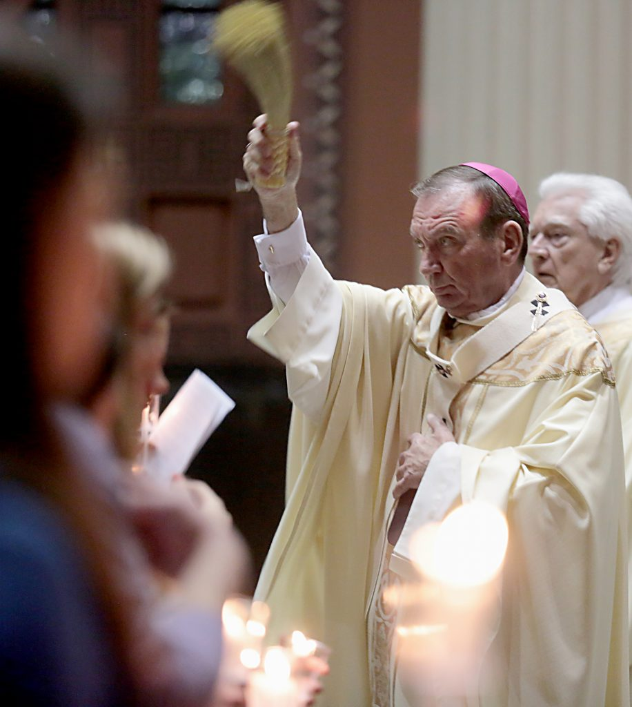 Archbishop Dennis Schnurr, with Deacon David Klingshirn, blesses the church with Holy Water for the Easter Vigil in the Holy Night at the Cathedral of Saint Peter in Chains in Cincinnati, Holy Saturday, March 31, 2018. (CT Photo/E.L. Hubbard)