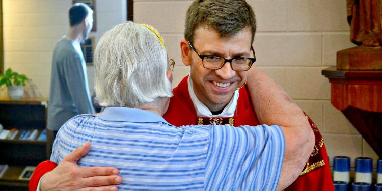 Rev. Craig Best receives a congratulatory hug from a parishioner at St. Margaret St. John (CT Photo/Greg Hartman)