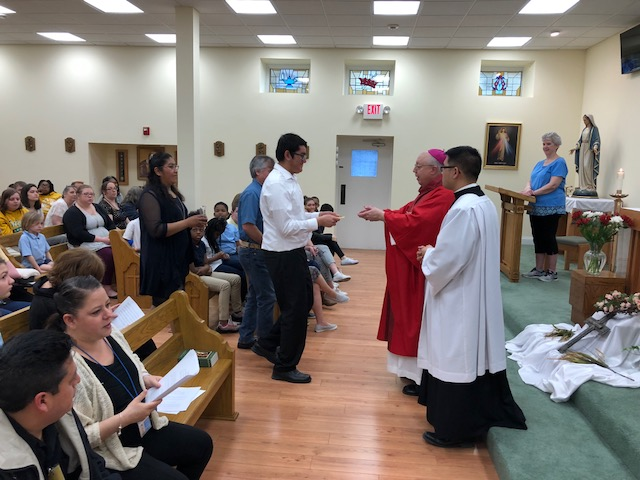 Bishop Joseph Binzer (right) celebrates confirmation for Roberto (center), a deaf Mexican teen studying at St. Rita School for the Deaf. (Courtesy Photo)