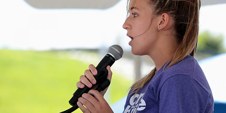 """Allison Riegler sings """"God Bless America"""" during the Cross the Bridge for Life celebration on Riverboat Row in Newport, Sunday, June 3, 2018. (CT Photo/E.L. Hubbard)"""