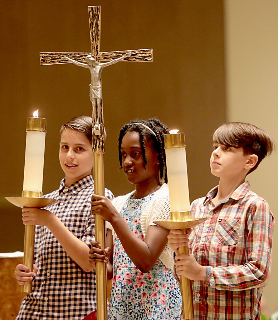 Max Fink, 12, Kenya Howard, 10, and Jake Fink, 10, lead the procession for the first annual Laudato Si' Community recognitions ceremony at Good Shepherd Church in Cincinnati Monday, June 18, 2018. (CT Photo/E.L. Hubbard)