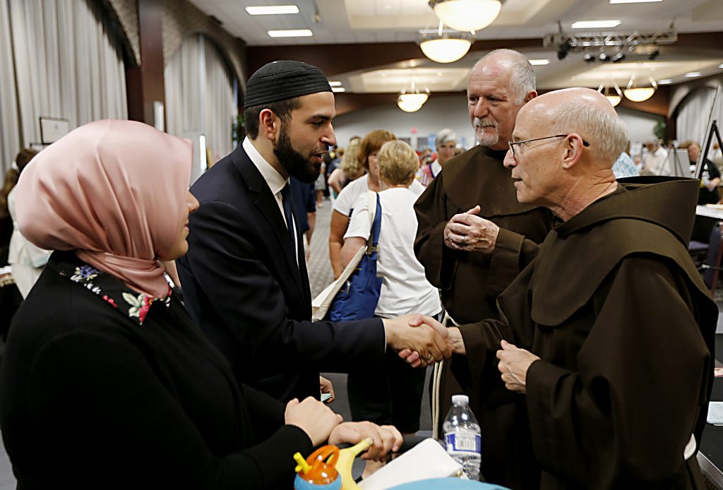 Jasnim Salem and her husband, Jammam Alwan, members of the Islamic Center of Greater Cincinnati, chat with Brother Timothy Lamb, OFM, and Father Bill Farris, OFM, during the first Festival of Faiths at the Cintas Center in Cincinnati Sunday, June 24, 2018. (CT Photo/E.L. Hubbard)