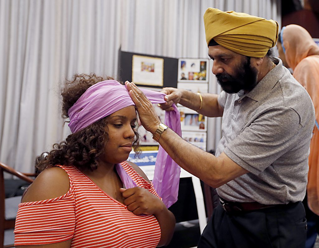 Jarvis Graham, from Legacy Pointe Church, has a turban fitted for her by Avatar Singh, a member of Sikh Gurdwara of Greater Cincinnati, during the first Festival of Faiths at the Cintas Center in Cincinnati Sunday, June 24, 2018. (CT Photo/E.L. Hubbard)