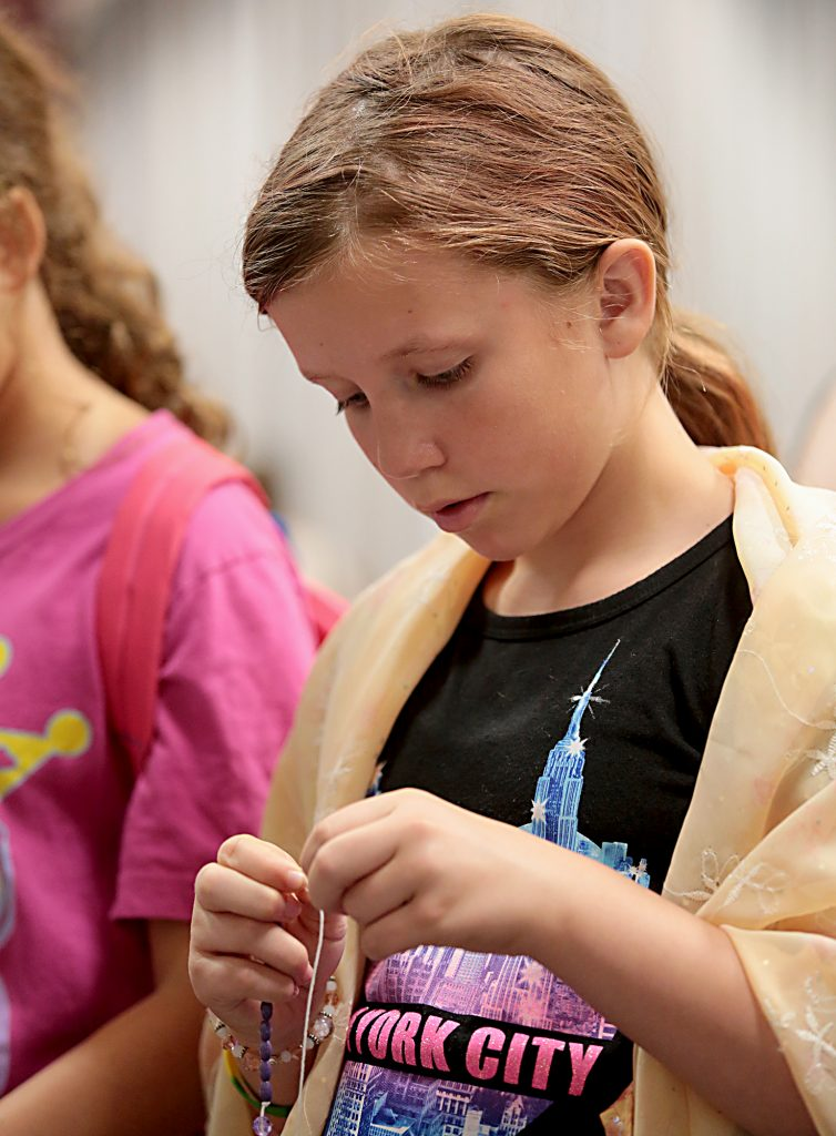Olivia Klefeker, 10, of the Catholic faith, wears a Muslim hijab on her shoulders as she makes a Rosary during the first Festival of Faiths at the Cintas Center in Cincinnati Sunday, June 24, 2018. (CT Photo/E.L. Hubbard)