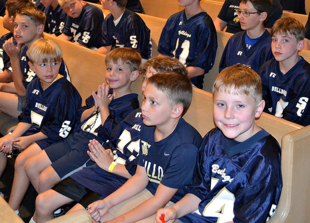 Boys from the St. Gertrude Football squad await praying the rosary. (CT Photo/Greg Hartman)