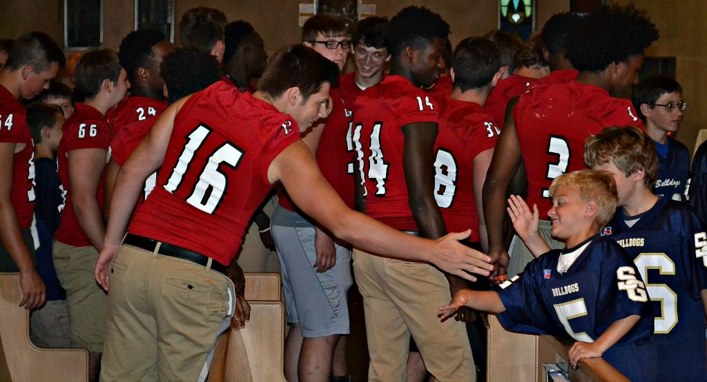 After the rosary, some of the La Salle Football Team shake hands and high five players from the St. Gertrude Football Team (CT Photo/Greg Hartman)