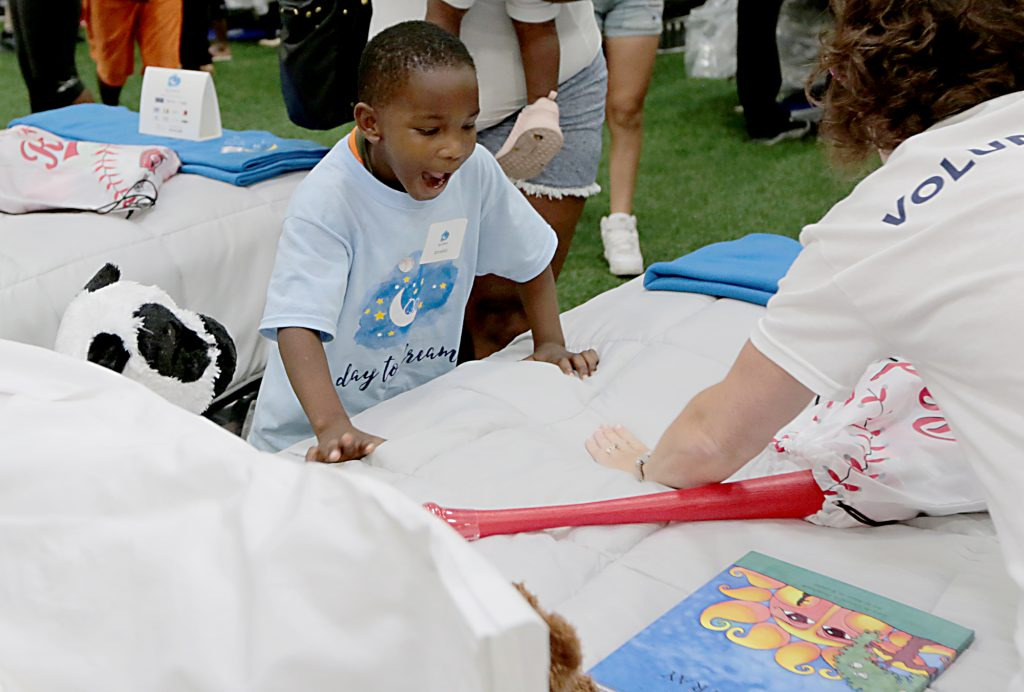 """Ahnekko Wills reacts to getting a new bed during the second annual """"Day to Dream"""" event at the P&G MLB Cincinnati Reds Youth Academy in Roselawn Saturday, Aug. 25, 2018. St. Vincent de Paul - Cincinnati and Morris Furniture Company teamed up to provide 50 children in need with a bed of their own. (CT Photo/E.L. Hubbard)"""
