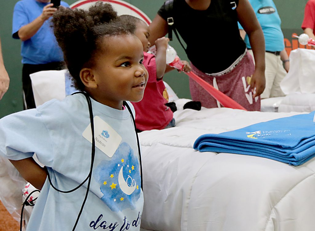 """Nadeon Fitzgerald puts on her new backpack during the second annual """"Day to Dream"""" event at the P&G MLB Cincinnati Reds Youth Academy in Roselawn Saturday, Aug. 25, 2018. St. Vincent de Paul - Cincinnati and Morris Furniture Company teamed up to provide 50 children in need with a bed of their own. (CT Photo/E.L. Hubbard)"""