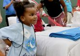 "Nadeon Fitzgerald puts on her new backpack during the second annual ""Day to Dream"" event at the P&G MLB Cincinnati Reds Youth Academy in Roselawn Saturday, Aug. 25, 2018. St. Vincent de Paul - Cincinnati and Morris Furniture Company teamed up to provide 50 children in need with a bed of their own. (CT Photo/E.L. Hubbard)"