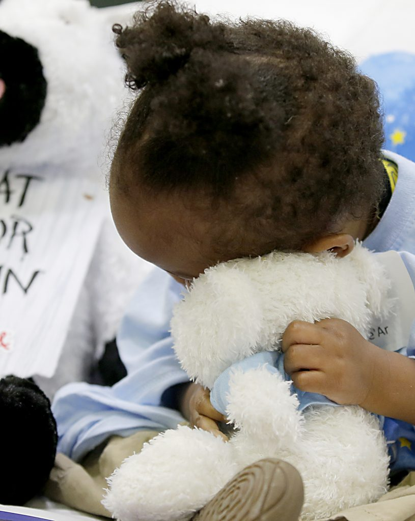 """She'Ar McBeth buries her face into her new plush animal during the second annual """"Day to Dream"""" event at the P&G MLB Cincinnati Reds Youth Academy in Roselawn Saturday, Aug. 25, 2018. St. Vincent de Paul - Cincinnati and Morris Furniture Company teamed up to provide 50 children in need with a bed of their own. (CT Photo/E.L. Hubbard)"""