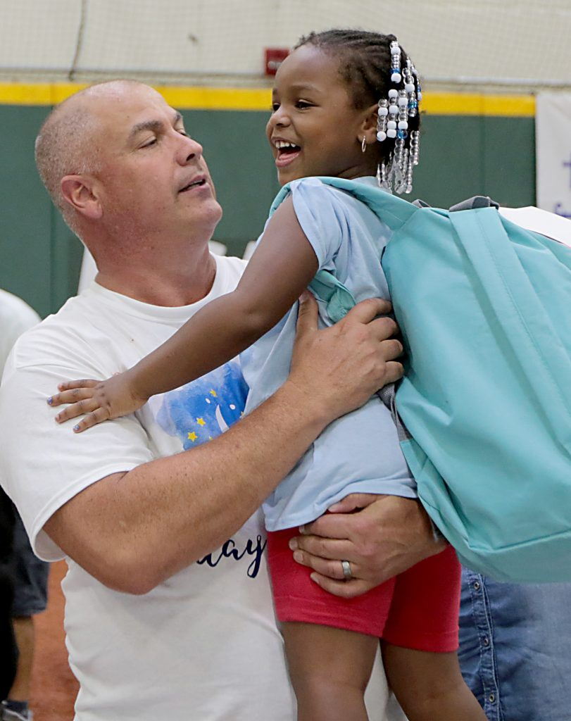 """Volunteer Steve Rowland lifts up Khalimah Bowens during the second annual """"Day to Dream"""" event at the P&G MLB Cincinnati Reds Youth Academy in Roselawn Saturday, Aug. 25, 2018. St. Vincent de Paul - Cincinnati and Morris Furniture Company teamed up to provide 50 children in need with a bed of their own. (CT Photo/E.L. Hubbard)"""
