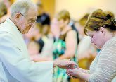 Father William Dorrmann delivers the Holy Eucharist to a parishioner during the St. Aloysius Parish 150th Anniversary Mass in Shandon Saturday, June 2, 2018. (CT Photo/E.L. Hubbard)