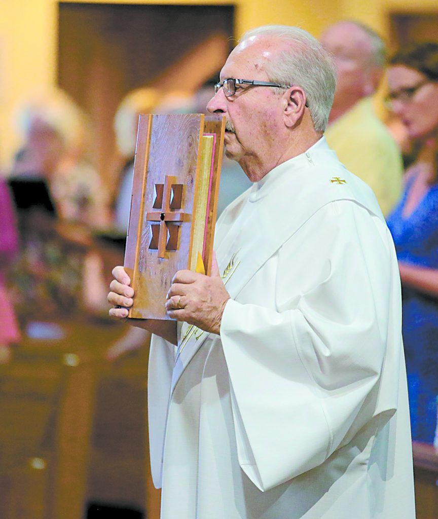 Deacon Bill Brunsman carries the Holy Bible during the processional for the St. Aloysius Parish 150th Anniversary Mass in Shandon Saturday, June 2, 2018. (CT Photo/E.L. Hubbard)