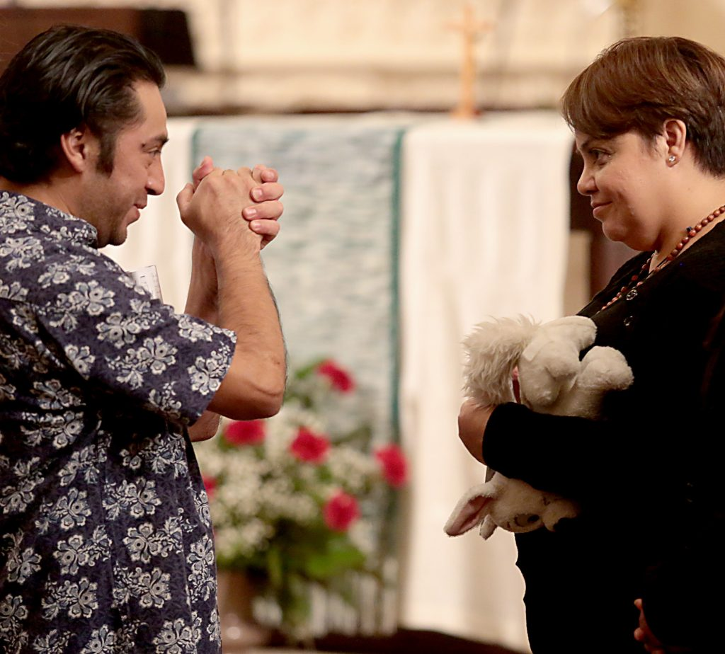 Maribel Trujillo Diaz, right, is greeted by a parishioner after the Prayer of Thanksgiving at St. Julie Billiart Parish in Hamilton Tuesday, Sept. 25, 2018. (CT Photo/E.L. Hubbard)