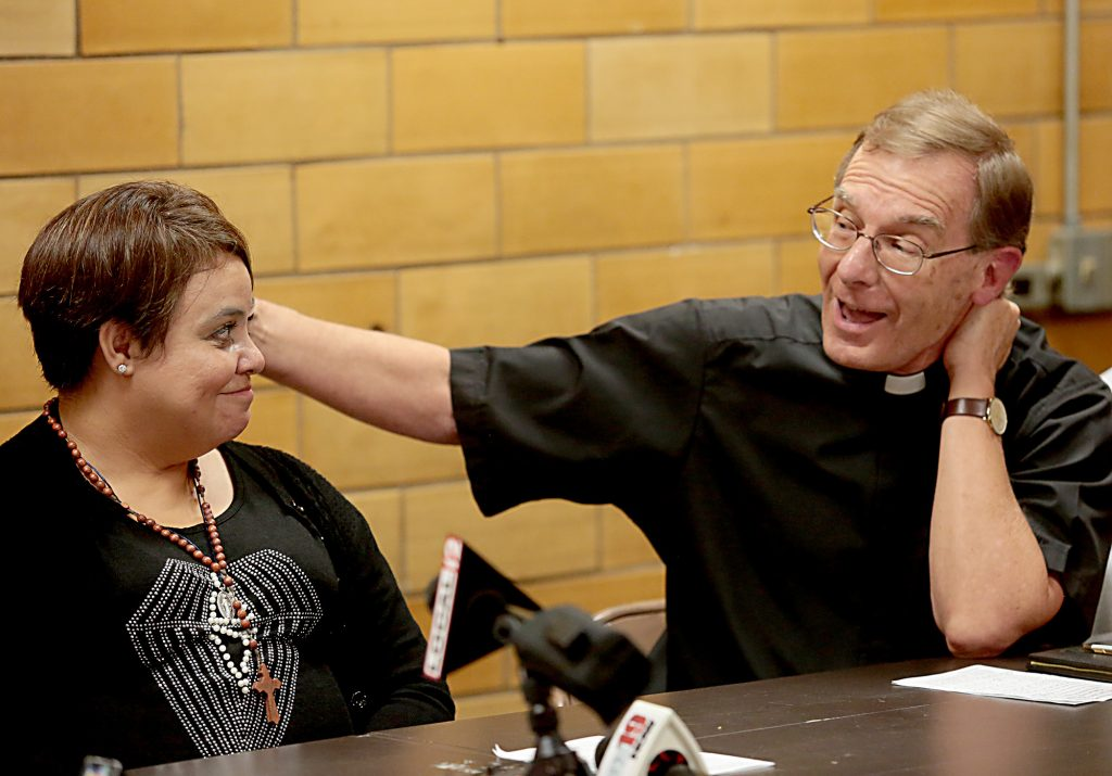 Maribel Trujillo Diaz listens as Fr. Mike Pucke talks about her seventeen month separation from her family after the Prayer of Thanksgiving at St. Julie Billiart Parish in Hamilton Tuesday, Sept. 25, 2018. (CT Photo/E.L. Hubbard)